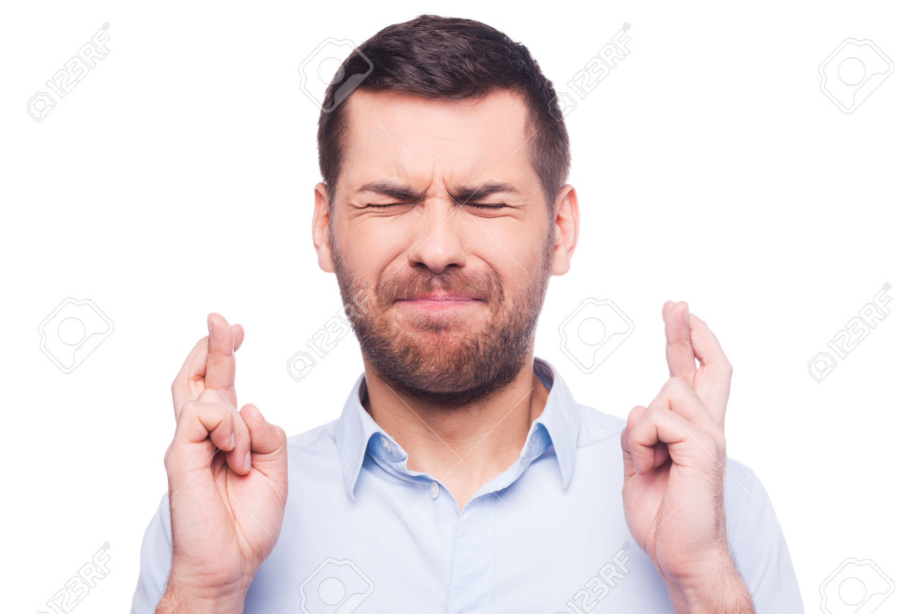 35528938-Portrait-of-young-man-in-shirt-keeping-fingers-crossed-and-eyes-closed-while-standing-against-white--Stock-Photo.jpg
